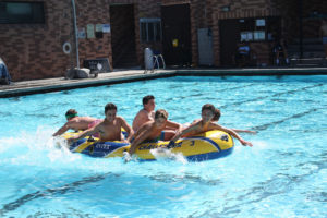 FIRST-YEAR STUDENTS swim across Conn Pool in a raft during the Olympic Gams, a variety of physical activities that help break the ice in each Big Brother retreat group and provide a fun introduction to the annual spiritual retreat.