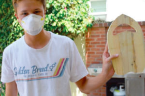 JUNIOR LACHLAN BONESTEEL holds upp a near-complete Pappy Surf handplane. The non-profit was founded in 2015.